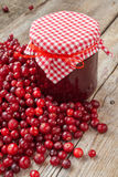Jar of jam and fresh red cranberries on wooden table. Royalty Free Stock Photos