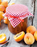 Jar of jam and ripe apricot fruits on table Royalty Free Stock Images