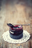 Jar of jam with spoon on old wooden table. Stock Images