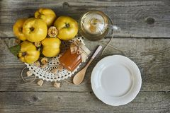 empty plate with jar of jam and quinces on rustic wooden background royalty free stock photography