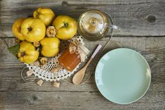 empty plate with jar of jam and quinces on rustic wooden background stock image