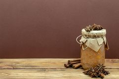Jar of jam stars anise and cinnamon sticks to Brown and a wooden background royalty free stock photography