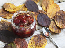 Jar of jam on the table with leaves. Jar of jam on the wooden table with yellow autumn leaves royalty free stock photography