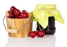 Jar of jam a wooden bucket with sweet cherries Royalty Free Stock Photo