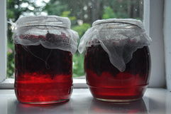Jar, jars of jam with red currants standing on the windowsill in the farmhouse. Stock Image
