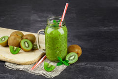 A jar of kiwi juice on a black table background. Fresh kiwi fruits on a cutting desk. Healthy green juice. Copy space. Stock Photo