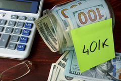 Jar with label 401k and money on the table. Royalty Free Stock Photo