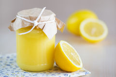 A jar of lemon curd with a  lemon Royalty Free Stock Photos