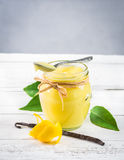 A jar of lemon curd on rustic background. Stock Photo