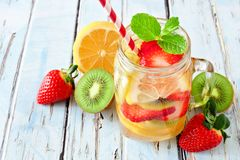 Jar of lemon, strawberry, kiwi detox water against blue wood Royalty Free Stock Photo