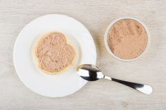 Jar with liver pate, bread with pate and teaspoon. Metallic jar with liver pate, bread with pate in plate and teaspoon on wooden table. Top view Royalty Free Stock Photo