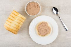Jar with liver pate, sandwich with pate, bread and teaspoon. Metallic jar with liver pate, sandwich with pate, bread and teaspoon on wooden table. Top view Stock Photo