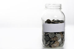 Jar of loose change. With blank label Royalty Free Stock Photos