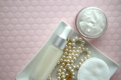 A jar of luxury beauty face cream and serum bottle with pearls on pink color background with copy space. Styled feminine lifestyle image Stock Image