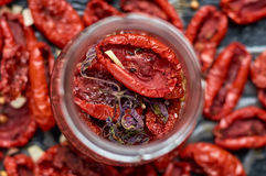 Jar with many dried red tomatoes and spices on a dark surface close up. Dried tomatoes texture blurred background Royalty Free Stock Photos