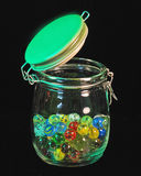 Jar of marbles. Jar containing multicolored glass marbles all isolated  on a dark background Stock Photo
