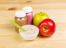 Jar mashed,  bowl  oatmeal and apples on  background light wood. Royalty Free Stock Images