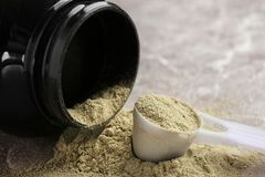 Jar and measuring spoon with hemp protein powder. On table stock photo