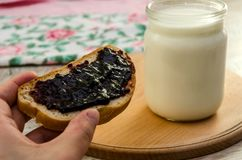 Jar of milk, bread spread with jam, on a wooden board stock images