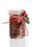 Jar Mincemeat. Jar of Christmas mincemeat tied with a festive ribbon with holly and berries on a white background Royalty Free Stock Image