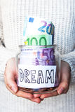 A jar with money. And coins in hands royalty free stock photo