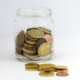 Jar with Money Small Change. A glass jar, isoleted on white, containing loose change money (euro coin), with breading, open Stock Image