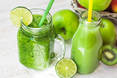 Jar mug with green vegetable smoothie and fruit juice in bottle with straw, apples, lime, kiwi,outdoors Royalty Free Stock Photography