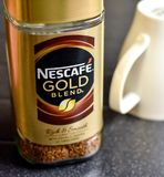 Nescafe Gold Blend instant coffee and cup. A jar of Nescafe gold blend coffee with an upturned cup ready for making a hot drink Royalty Free Stock Image
