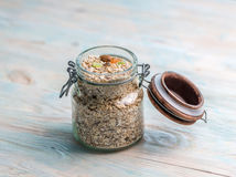 Jar of oatmeal with raisins and nuts. Jar full of oatmeal with raisins and nuts, some dried fruits open, some scattered Stock Photos