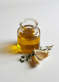 A jar of oil, two garlic cloves and a savory twig Stock Images