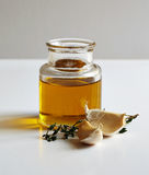 A jar of oil, two garlic cloves and a savory twig Royalty Free Stock Image