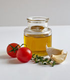 A jar of oil, two garlic cloves, tomatoes and a savory twig Royalty Free Stock Image