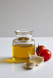 A jar of oil, two garlic cloves and tomatoes Stock Photo
