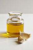 A jar of oil and two garlic cloves Royalty Free Stock Photos