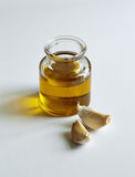 A jar of oil and two garlic cloves Royalty Free Stock Image