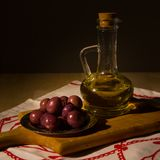 Jar with olive oil and some olives. Over black  background Royalty Free Stock Photography