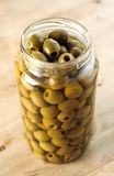 Jar of Olives. Large glass jar stuffed full of Olives on wooden table stock images