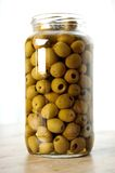 Jar of Olives. Large glass jar stuffed full of Olives on wooden table Royalty Free Stock Images
