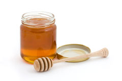 Jar of open honey with drizzler. Over white Royalty Free Stock Photo