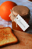 Jar of orange marmalade with orange. Jar of orange marmalade and toast with orange on a wooden board, a white lace tablecloth Royalty Free Stock Photos