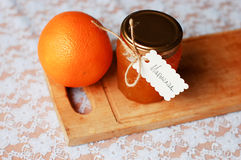 Jar of orange marmalade and toast with orange. On a wooden board, a white lace tablecloth Stock Photo