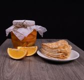 A jar of orange syrup with orange slices next to a plate of fried pancakes on a wooden surface with a black background royalty free stock image