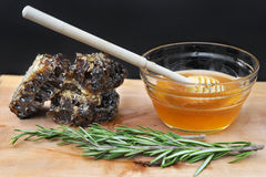 Jar with organic honey, honeycomb and rosemary on wood and black Stock Images