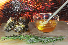 Jar with organic honey and a rosemary on wood with honeycomb as Stock Photo
