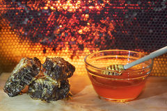 Jar with organic honey on wood with honeycomb background Royalty Free Stock Photography