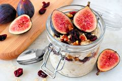 Jar of overnight autumn oats with figs, cranberries and walnuts Royalty Free Stock Photos