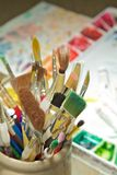 Jar of Paintbrushes. A cermaic jar filled with a variety of paint brushes.  The artists color mixing tray can be seen in the background Stock Photography