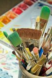 Jar of Paintbrushes (Right). A ceramic jar filled with paintbrushes is in the foreground, justified to the right side, with the artists color mixing tray in the Stock Images