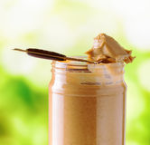Jar of peanut butter on nature background Royalty Free Stock Images