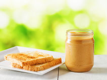 Jar of peanut butter and toasts on nature background Royalty Free Stock Image